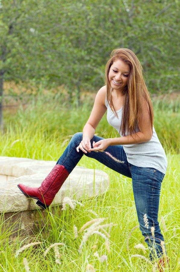 Calças de brim da menina adolescente e carregadores de cowboy desgastando imagem de stock