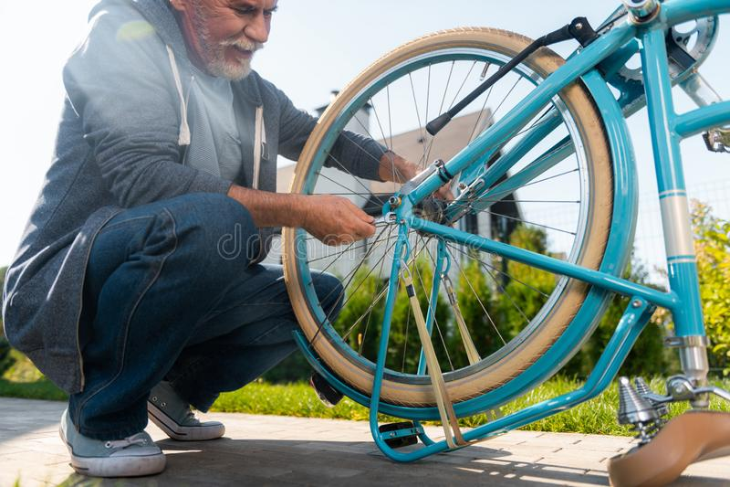 Calças de brim do homem maduro farpado e revestimento de esporte vestindo que repara sua bicicleta azul foto de stock
