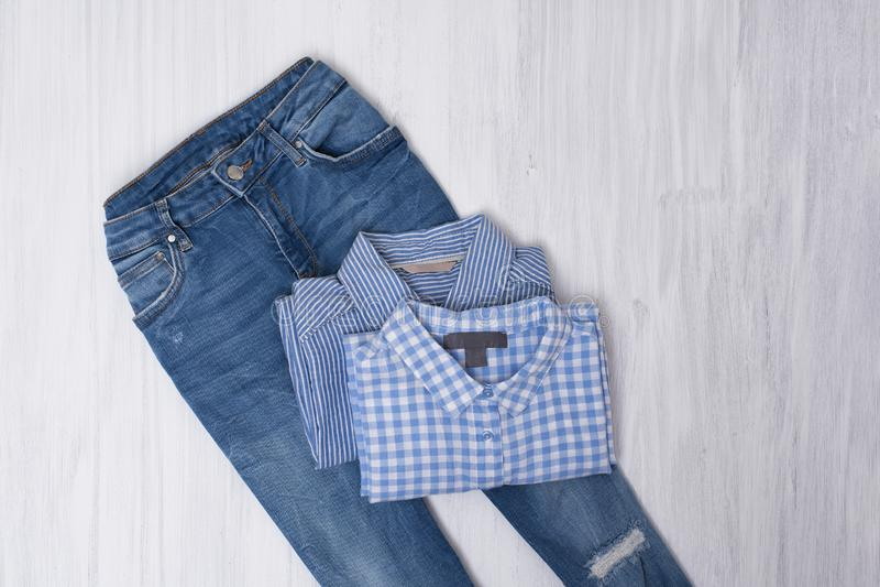 Calças de brim e camisas rasgadas azuis no fundo de madeira C elegante foto de stock royalty free