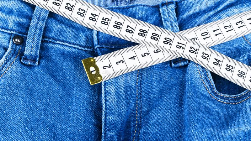 Calças de brim e régua de uma mulher do azul, conceito da dieta e perda de peso Calças de brim com fita de medição Estilo de vida fotografia de stock