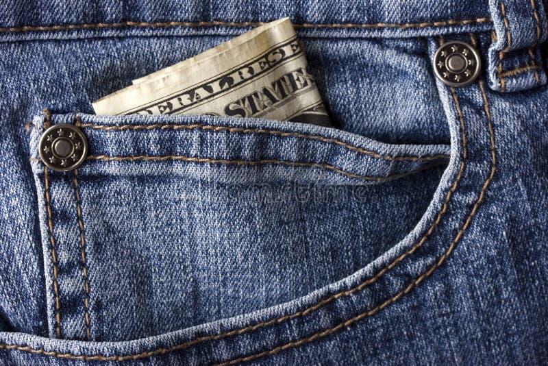 Calças de brim e uma conta de dólar imagem de stock