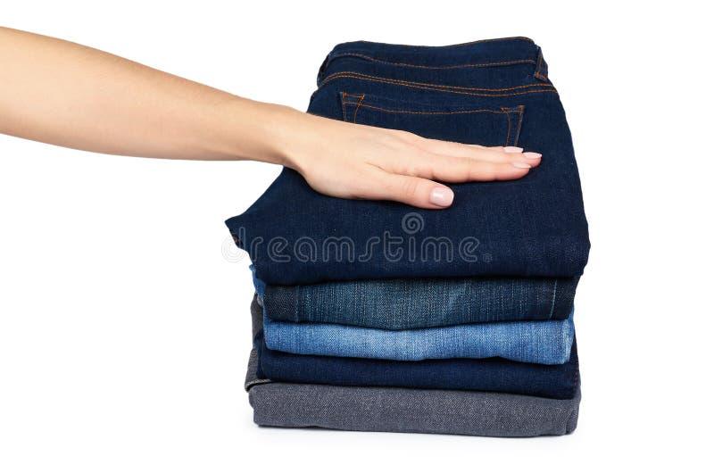 Calças de brim de Foldet na pilha com a mão, isolada no fundo branco foto de stock royalty free
