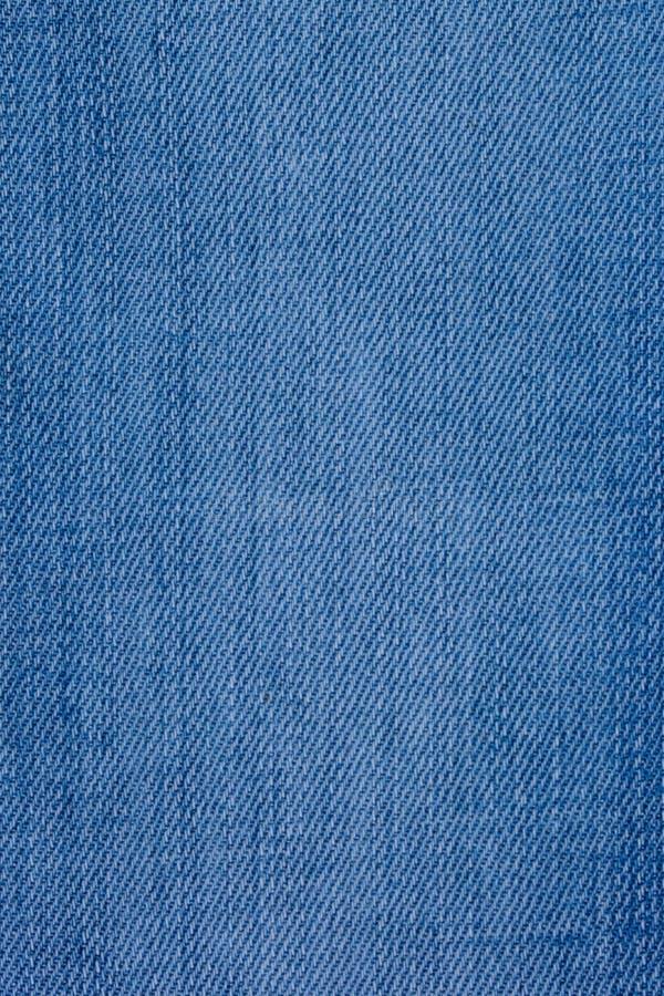 Calças de brim materiais com uma cor áspera do azul da textura foto de stock