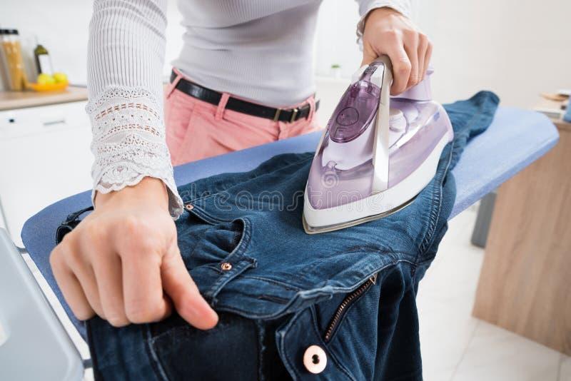 Calças de brim passando da mulher foto de stock