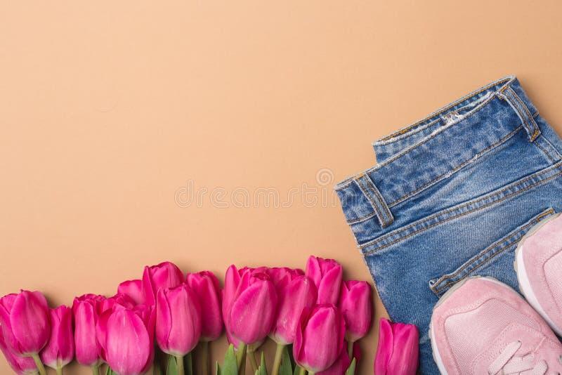 Calças de brim, sapatilhas e tulipas cor-de-rosa Configuração lisa Conceito da mola da forma Espaço livre Copie o espaço fotos de stock
