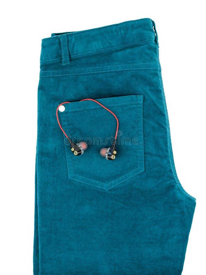 Calças de brim verdes com os fones de ouvido no bolso isolado no fundo branco foto de stock royalty free