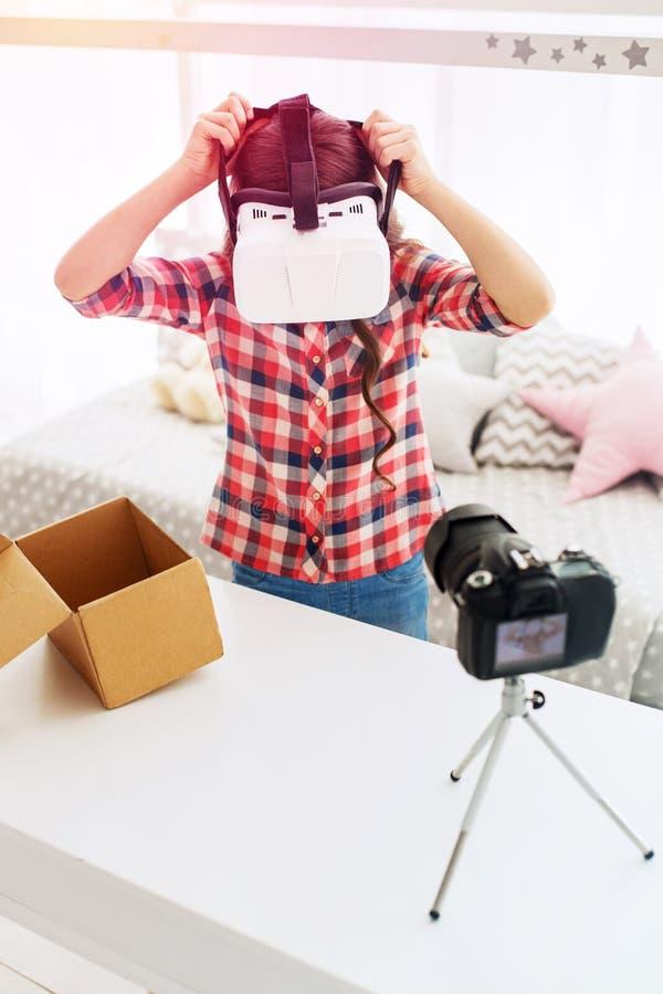 Calças de brim vestindo da menina pré-escolar e camisa esquadrada que tentam seus vidros novos da realidade virtual foto de stock royalty free