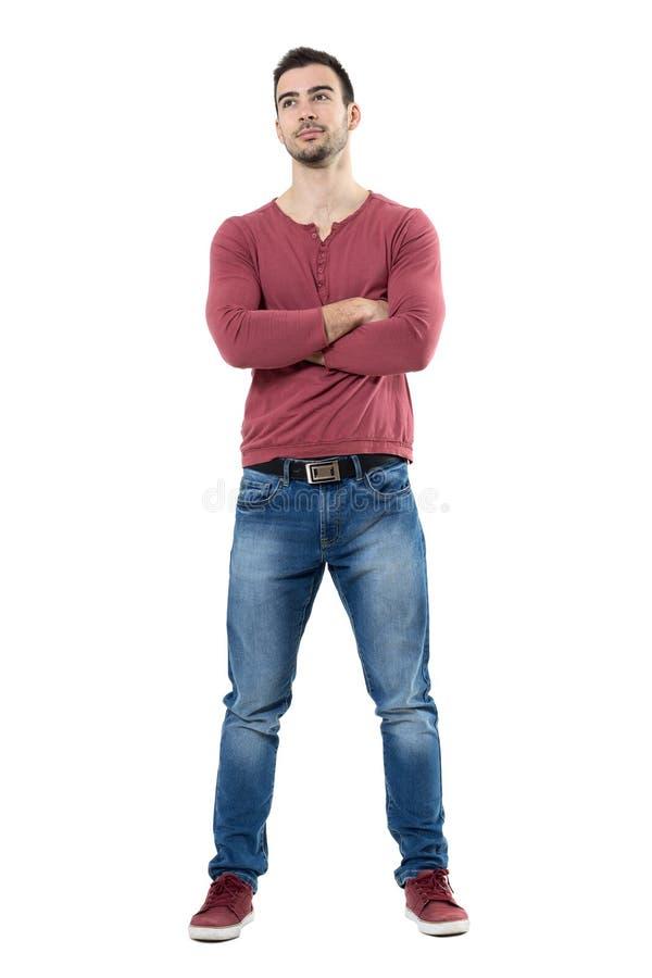Calças de brim vestindo de sorriso do homem ocasional dos jovens felizes com os braços cruzados que olham acima foto de stock royalty free