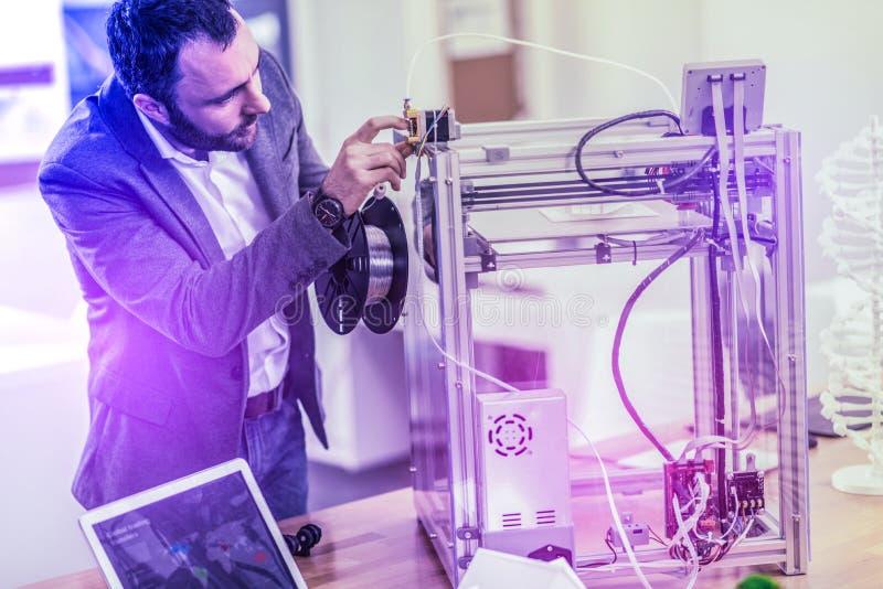 Calças de brim vestindo do homem de negócios farpado e posição escura do revestimento perto da impressora 3D imagem de stock