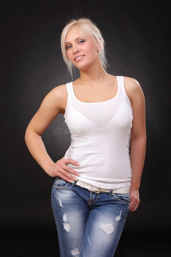calças de brim vestindo do louro e uma camiseta de alças Em um fundo preto fotografia de stock