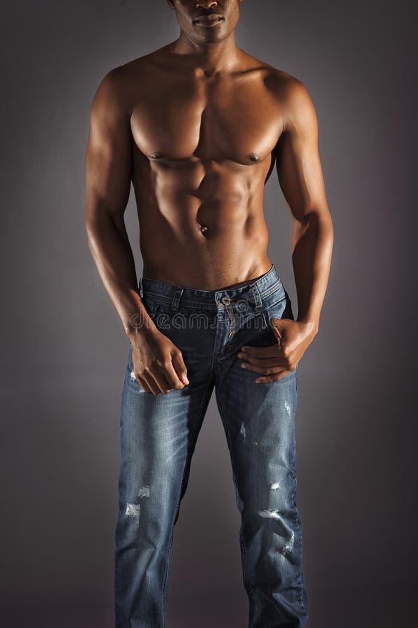 Calças de brim vestindo do modelo masculino africano imagem de stock
