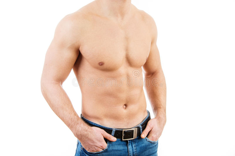 Calças de brim vestindo musculares do homem novo imagens de stock
