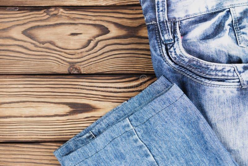 Calças de ganga com o bolso vazio na tabela marrom rústica de madeira velha foto de stock