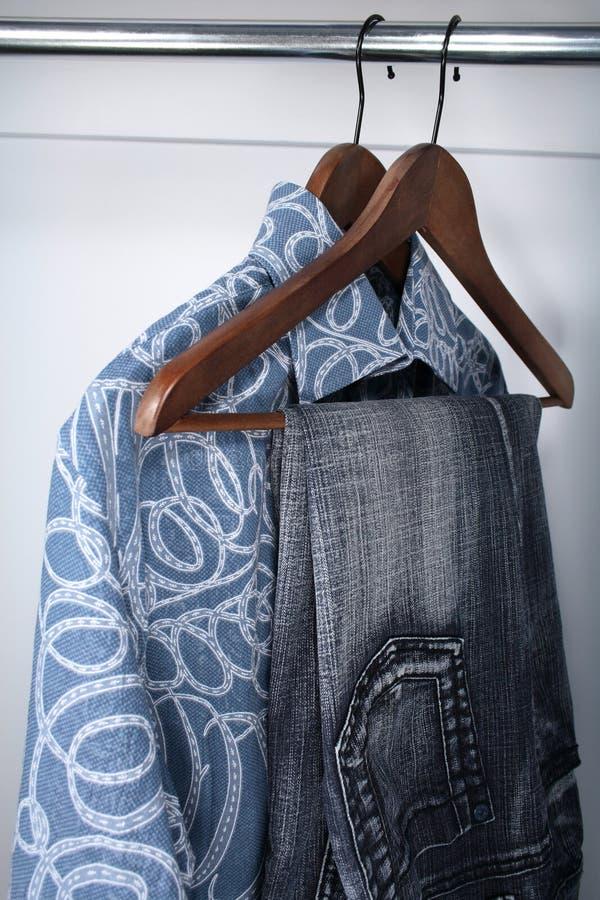 Calças de ganga e camisas em ganchos de madeira imagens de stock royalty free
