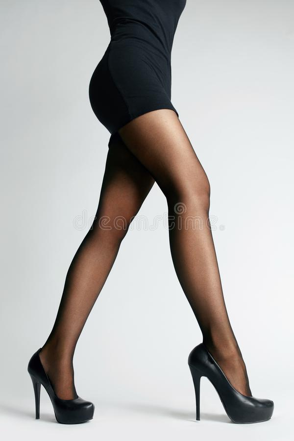 Calças justas pretas Pés fêmeas com meia-calça imagem de stock