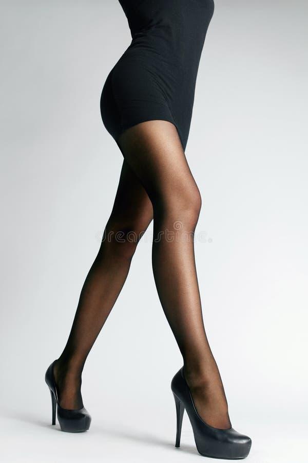 Calças justas pretas Pés fêmeas com meia-calça foto de stock royalty free