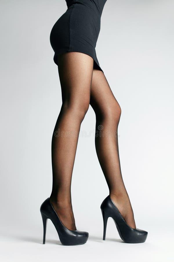 Calças justas pretas Pés fêmeas com meia-calça imagens de stock royalty free