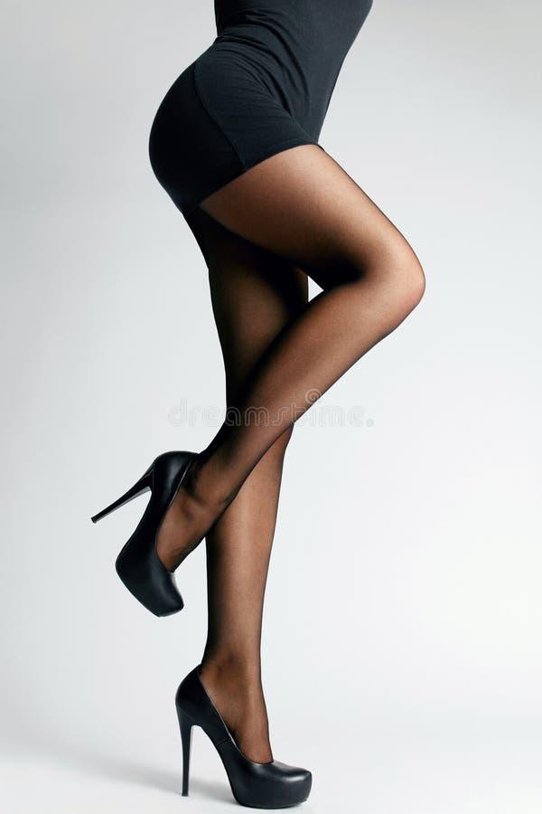 Calças justas pretas Pés fêmeas com meia-calça imagem de stock royalty free