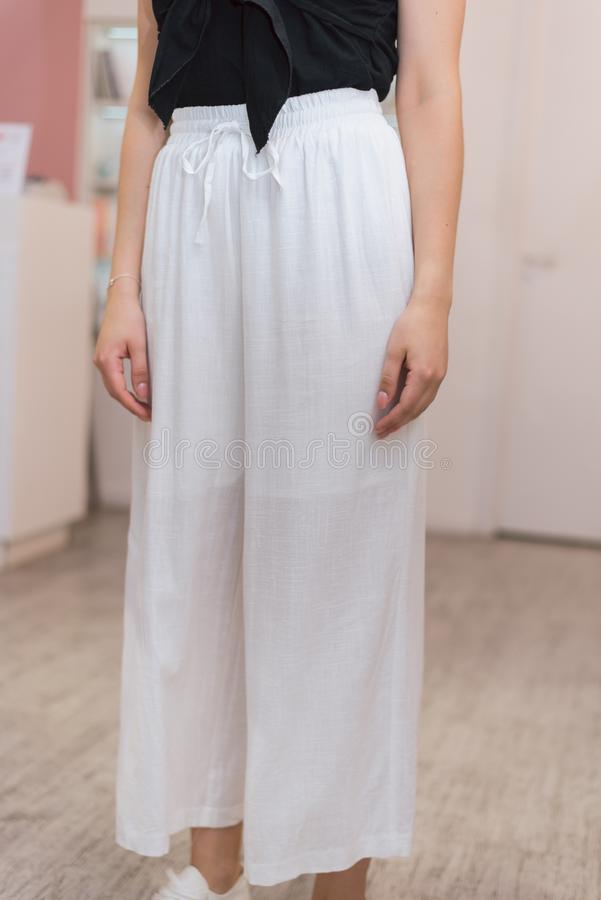 Calças leves leves na menina posição da moça na calças de linho elegante em um fundo cor-de-rosa na loja imagem de stock royalty free