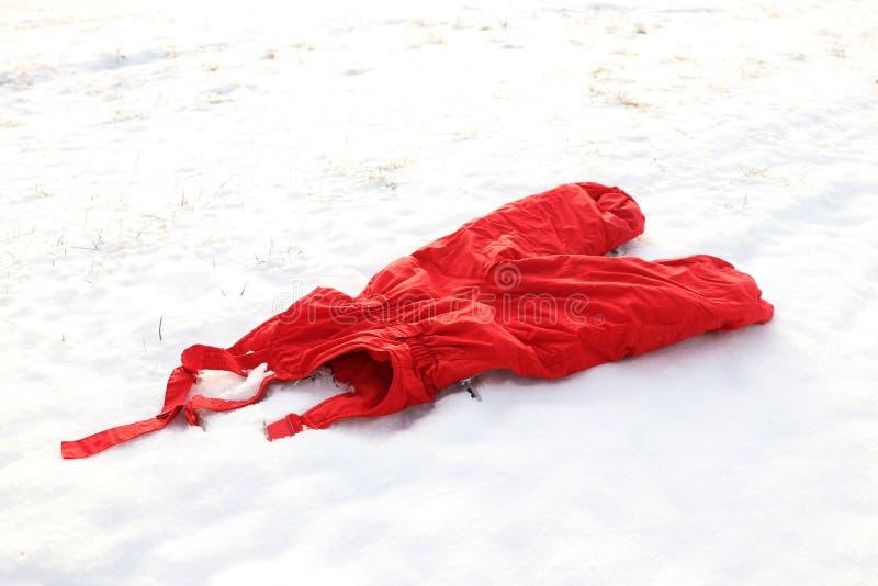 Calças morna vermelha dos salopettes na neve ou na cena do inverno imagem de stock