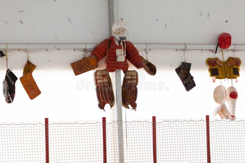 Calças protetoras velhas e outra proteção do goleiros que penduram na parede fotografia de stock royalty free