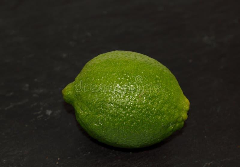 Cal exótico fresco verde dos citrinos em um fundo preto fotografia de stock