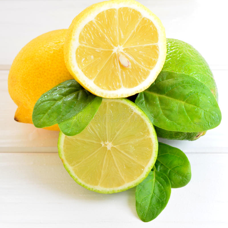 Cal y limón de la fruta cítrica en una tabla blanca imagenes de archivo