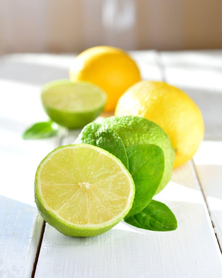 Cal y limón de la fruta cítrica en una tabla blanca fotografía de archivo