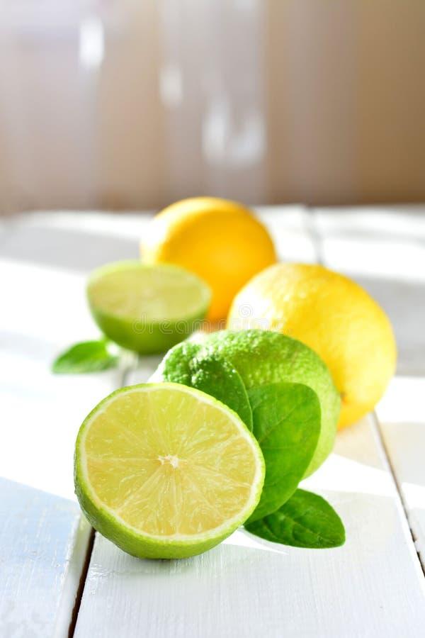 Cal y limón de la fruta cítrica en una tabla blanca fotografía de archivo libre de regalías