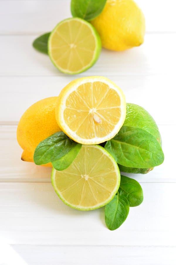 Cal y limón de la fruta cítrica en una tabla blanca foto de archivo libre de regalías