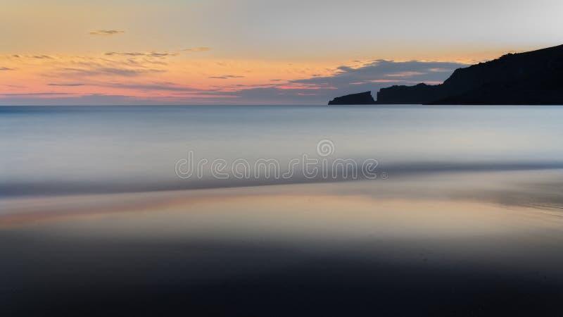 Cala Mesquida, alba, spiaggia, mar Mediterraneo, colline, rocce, riflessione dorata del sole su acqua, cielo blu con le nuvole, M fotografia stock libera da diritti