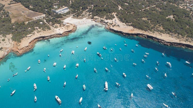 Cala Saona in Formentera island and many boats over turquoise sea . Many boats over turquoise sea and small cliff. Cala Saona in Formentera island stock photos