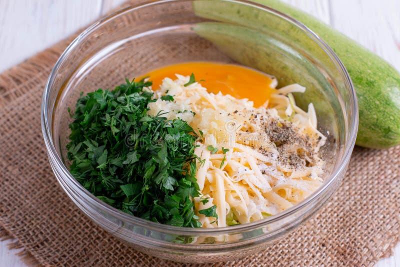 Calabacín, huevo, queso e hierbas rallados en un bol de vidrio foto de archivo