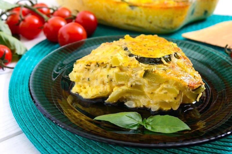 Calabacín, queso, huevos, crema y cazuela de los verdes en un fondo de madera blanco Porción de cazuela en una placa Sano sabroso imagen de archivo