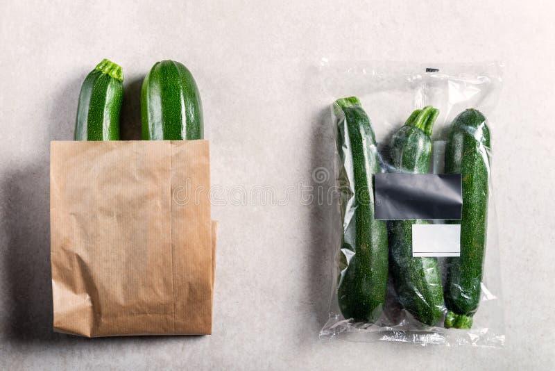 Calabacines en la bolsa de plástico CONTRA bolsa de papel Elija el concepto menos plástico fotografía de archivo libre de regalías
