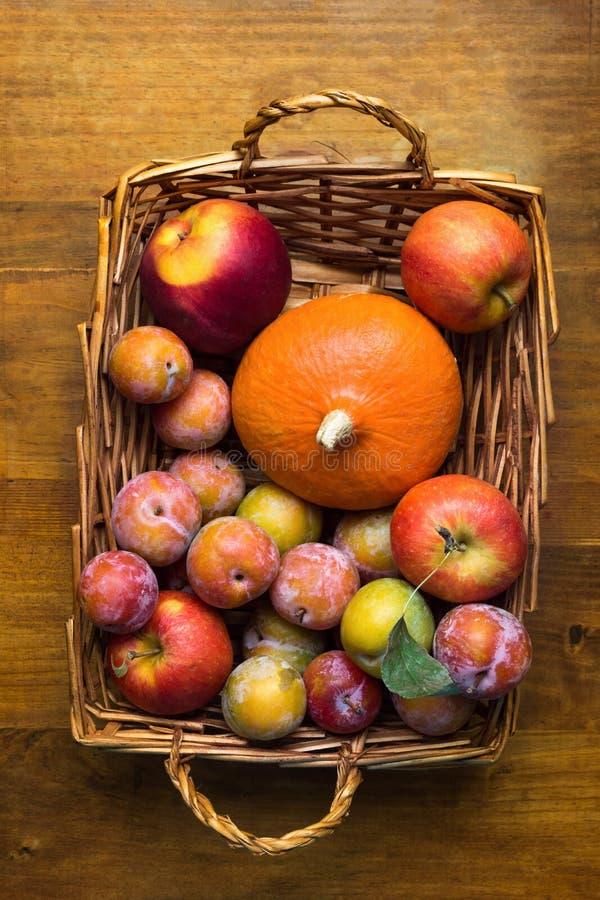 Calabaza anaranjada de las manzanas rojas del verde amarillo de los mirabeles de los ciruelos en cesta de mimbre en fondo de made imagenes de archivo