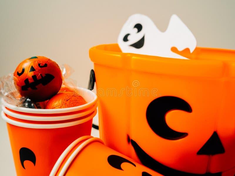 Calabaza anaranjada llenada de chocolates y de una taza anaranjada de la cartulina con la cara feliz y un fantasma blanco imagen de archivo libre de regalías