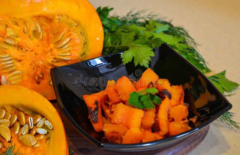 Calabaza cocida en un plato negro y rebanadas de calabaza con verdes Un plato delicioso del otoño fotografía de archivo libre de regalías