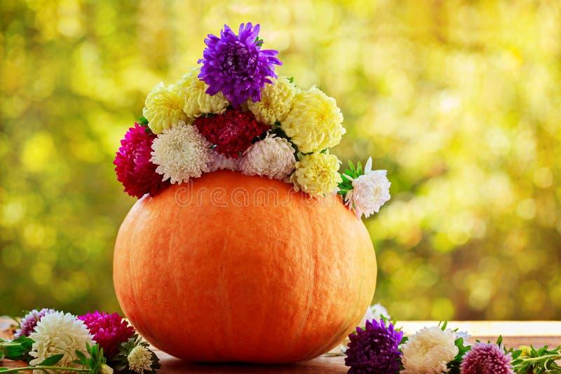 Calabaza con las flores coloridas en la tabla de madera contra fondo natural imagen de archivo