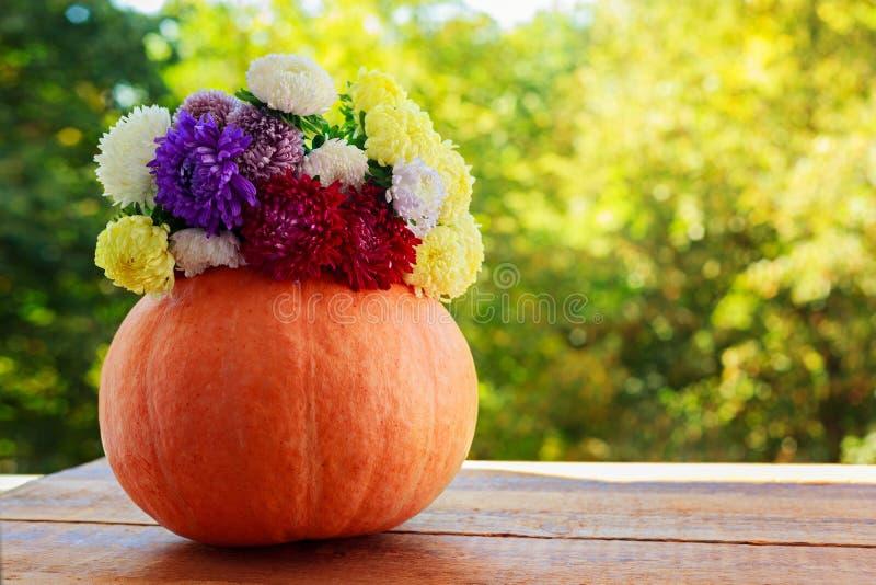 Calabaza con las flores coloridas en la tabla de madera contra fondo natural imagen de archivo libre de regalías