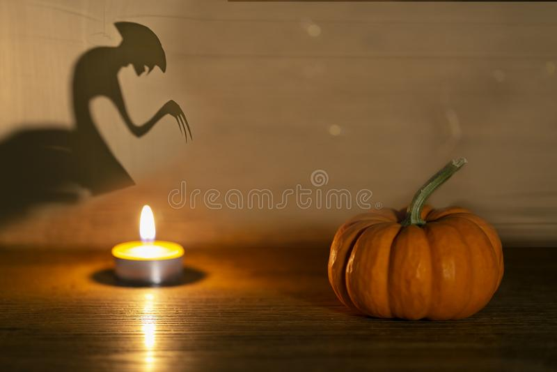 Calabaza de Halloween con fondo de madera viejo. Monstruo espiritual detrás. Concepto de teatro de sombra imagen de archivo