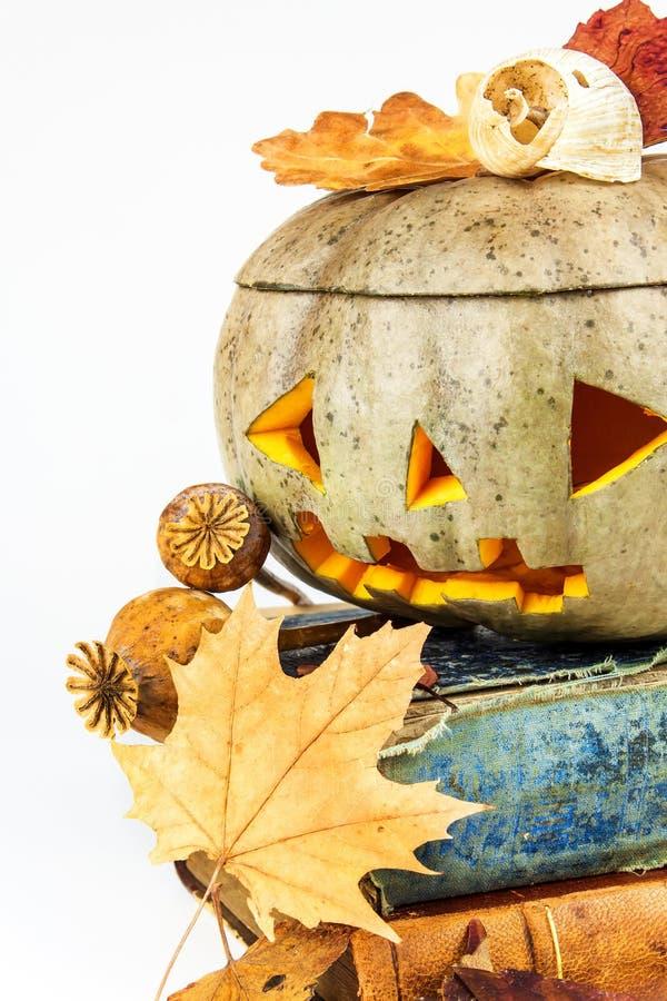 Calabaza de Halloween con los libros en el fondo blanco Calabaza de Halloween, linterna divertida del ` de Jack O Día de fiesta f foto de archivo libre de regalías