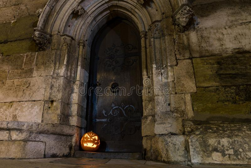 Calabaza de Halloween delante de la puerta de madera antigua y de la pared de piedra de una iglesia, Alemania foto de archivo libre de regalías