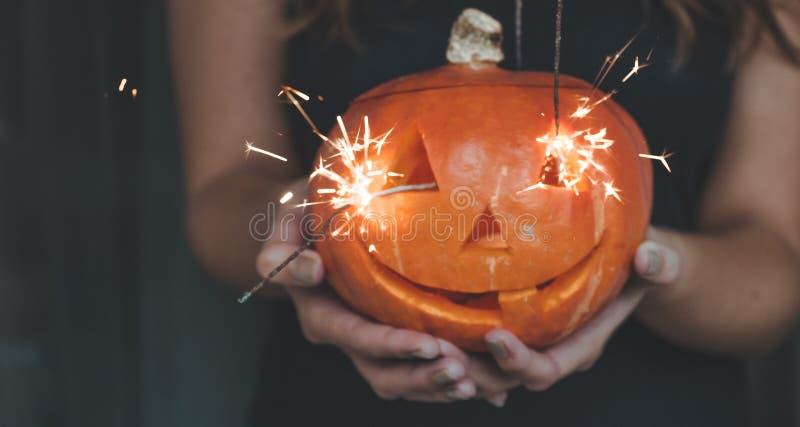 Calabaza de Halloween en las manos de una muchacha con las luces de Bengala Concepto de Halloween del día de fiesta Mujer hermosa foto de archivo