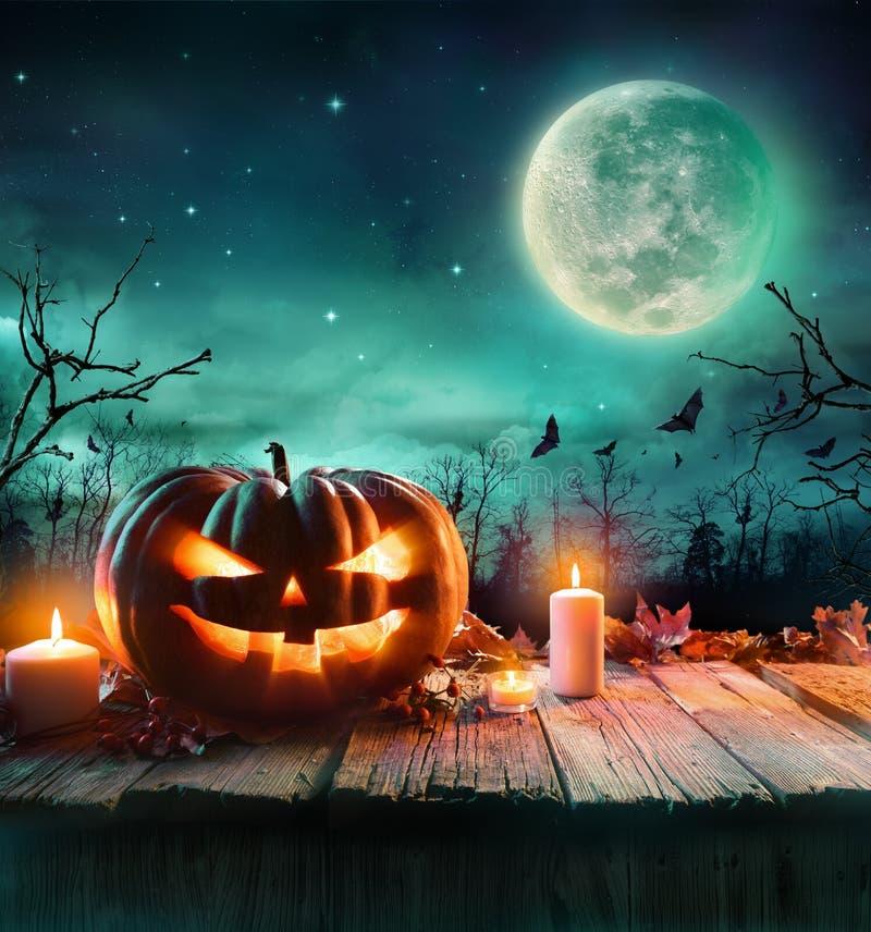 Calabaza de Halloween en un bosque fantasmagórico en la noche fotografía de archivo