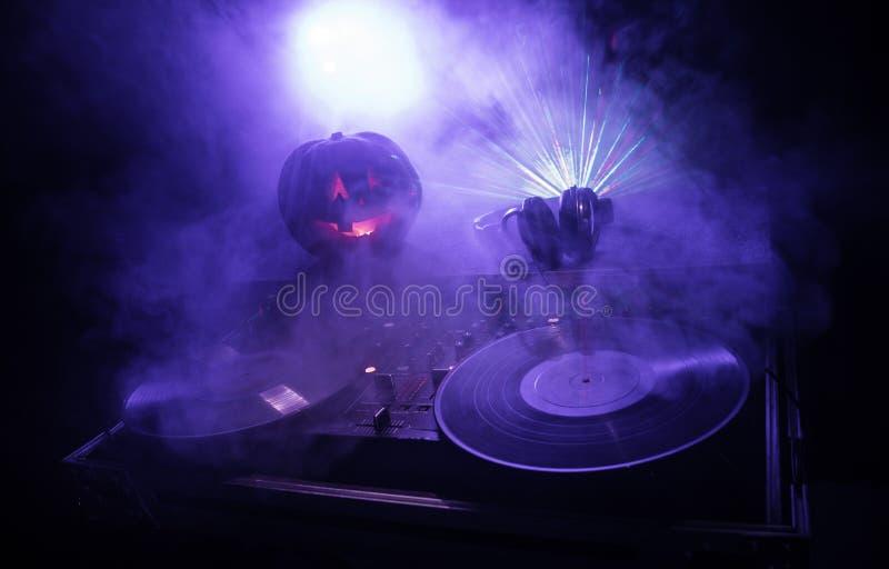 Calabaza de Halloween en una tabla de DJ con los auriculares en fondo oscuro con el espacio de la copia Decoraciones y música del fotografía de archivo libre de regalías