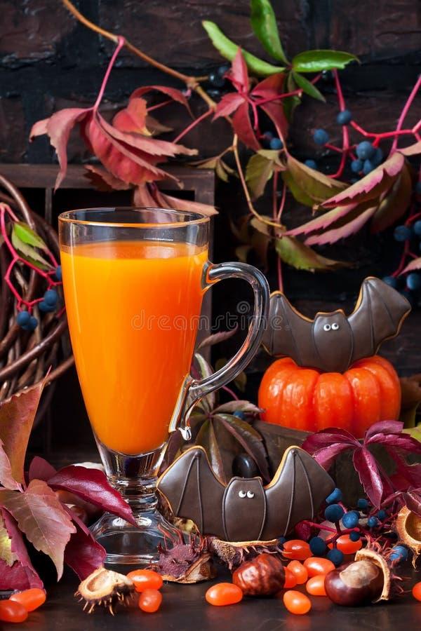 Calabaza de Halloween o jugo de zanahoria en vidrio en fondo oscuro imágenes de archivo libres de regalías