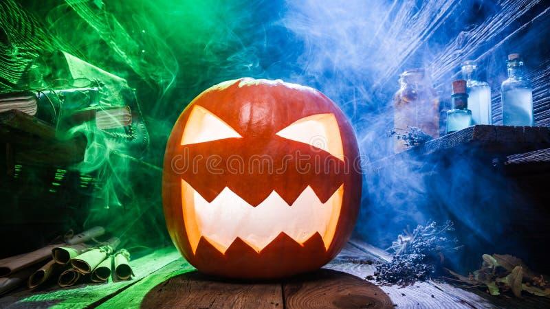 Calabaza de Halloween que brilla intensamente con humo azul y verde foto de archivo libre de regalías
