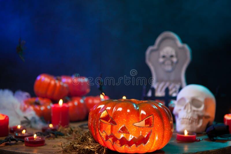 Calabaza de Halloween que brilla intensamente delante de un cráneo espeluznante en una tabla de madera fotos de archivo libres de regalías