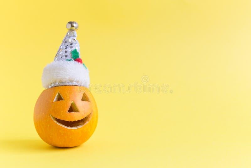 Calabaza de Halloween que lleva el sombrero de Santa Claus aislado en amarillo imagen de archivo libre de regalías